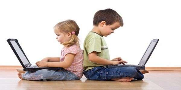 Little girl and boy using laptops